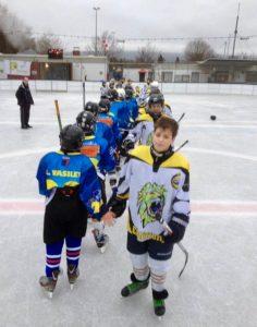 Jungen stehen beim Eishockey-Training in einer Reihe an