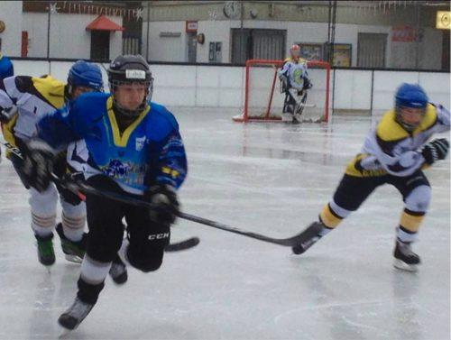 Jungen beim Eishockey auf der Eisbahn.