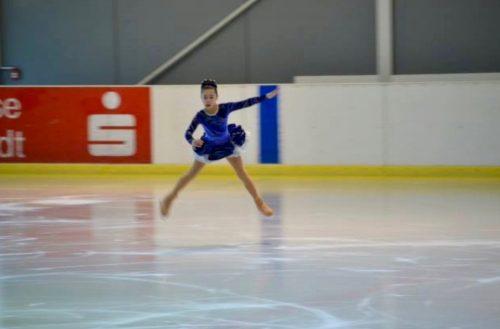 Eisläuferin in blau beim Sprung