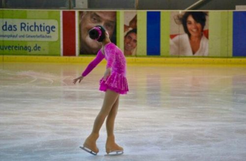 Eisläuferin in pink bei der Pirouette