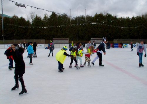 Die Tage nutzen: Eisläufer in bunten Kostümen bilden eine Polonaise